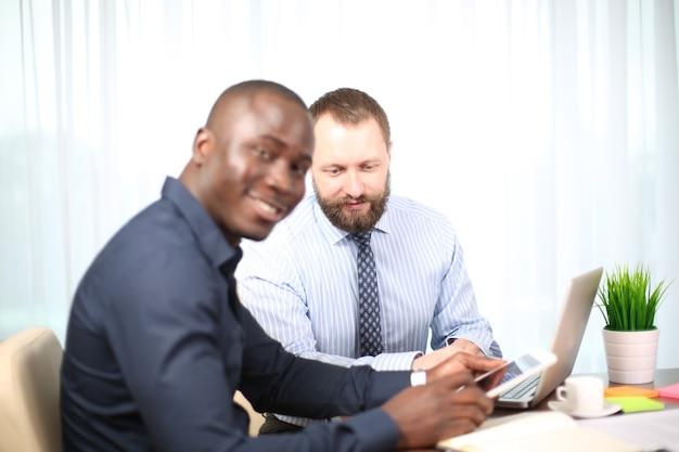 Empresário envelhecido sorridente, olhando para um colega na reunião de equipe, líder de equipe feliz e atencioso ouvindo uma nova ideia de projeto, mentor técnico