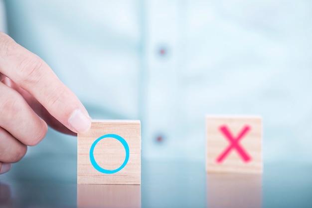 Empresário escolhe um sim ou não símbolos no cubo de madeira blogs, serviços e conceito de pesquisa de satisfação do cliente