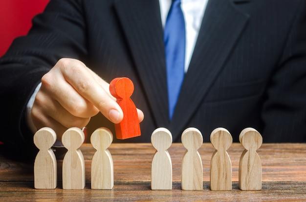 Empresário escolhe uma pessoa da equipe. o melhor funcionário, líder. liderança e promoção.