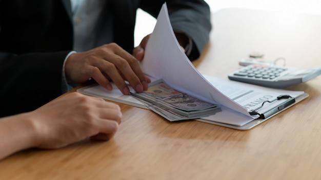 Empresário escondendo dinheiro em documentos para subornar funcionários do governo, o conceito de corrupção.