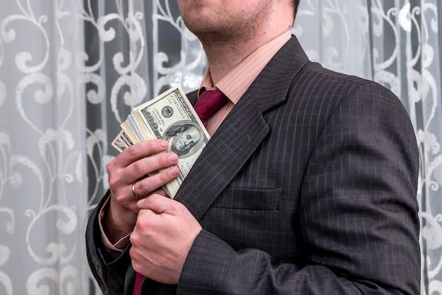 Empresário escondendo dinheiro em dólares no bolso da jaqueta