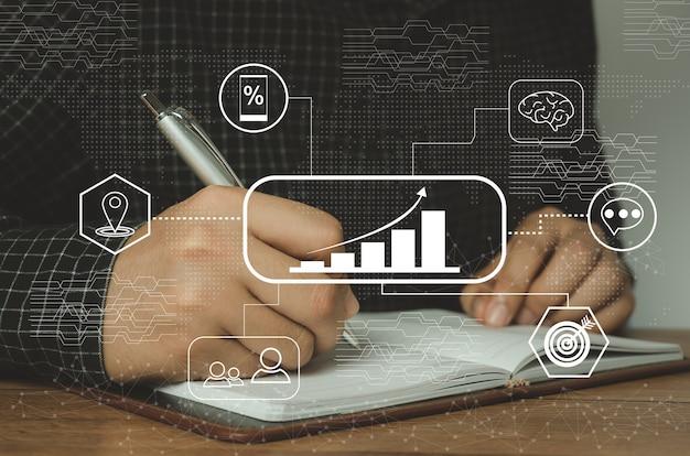 Empresário escreve no caderno com gráfico de ícones crescendo