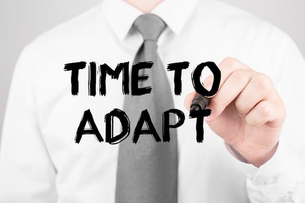 Empresário escrevendo a palavra hora de adaptar-se com marcador, conceito de negócio