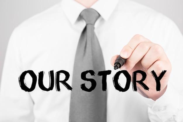 Empresário escrevendo a palavra nossa história com marcador, conceito de negócio