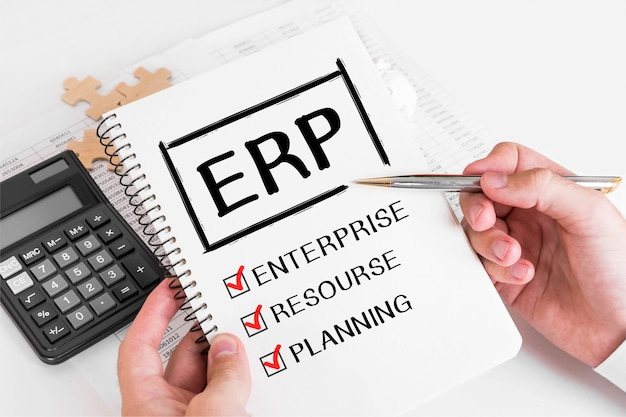 Empresário, escrevendo conceitos de erp em sua nota.