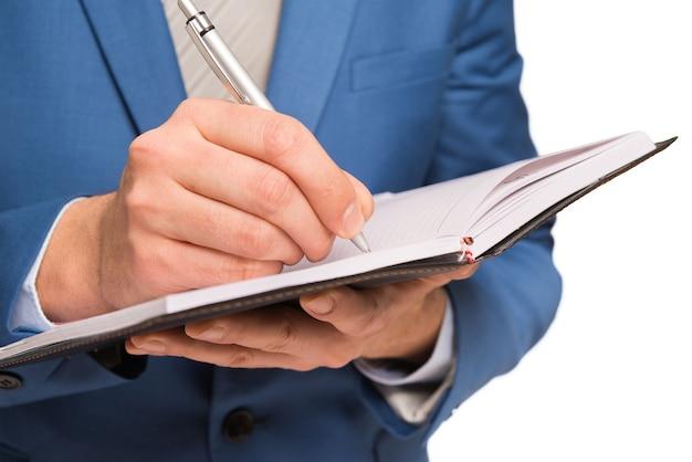 Empresário, escrevendo em sua agenda, isolado no branco