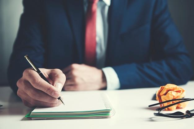 Empresário, escrevendo no bloco de notas com caneta na mesa