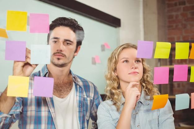 Empresário escrevendo no papel enquanto as mulheres lêem no escritório