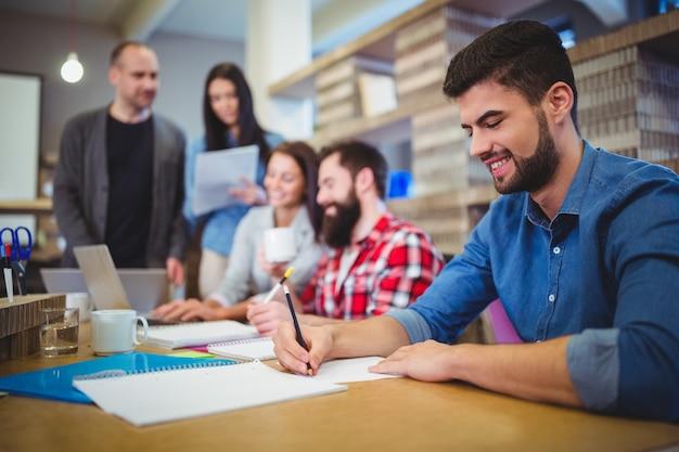 Empresário, escrevendo no papel enquanto colegas