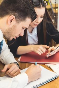 Empresário escrevendo um plano no papel, close-up. reunião de negócios