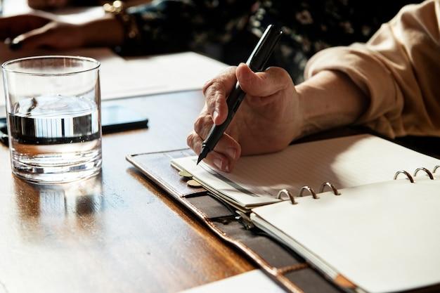 Empresário escrevendo uma nota da reunião