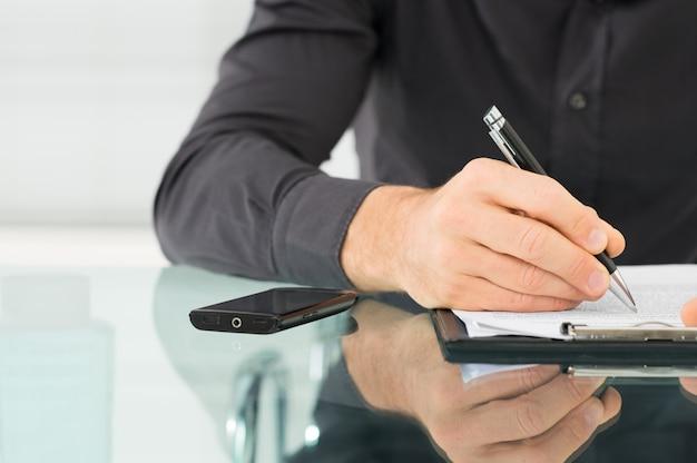 Empresário escrevendo uma papelada