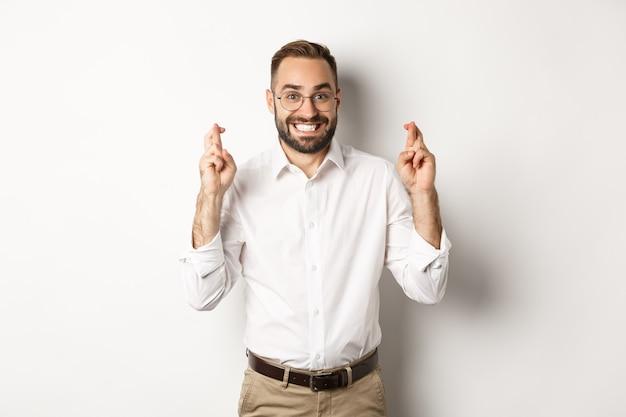Empresário esperançoso sorrindo e cruzando os dedos para dar sorte, fazendo um pedido, de pé