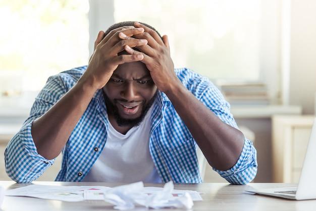 Empresário está apoiando-se nas mãos em desespero