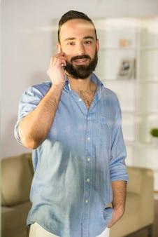 Empresário está falando por telefone, visto através do vidro.