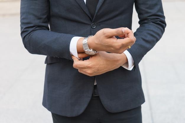 Empresário está mostrando o relógio dele.