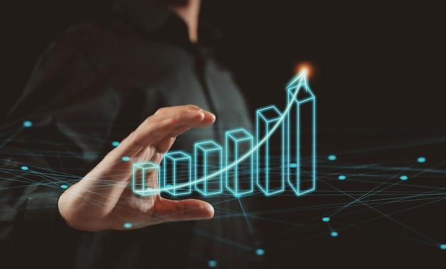 Empresário está segurando um gráfico crescente em fundo preto. o crescimento do negócio. conceito de progresso ou sucesso.