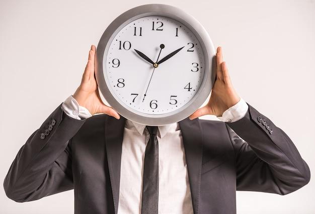 Empresário está segurando um relógio na frente da cabeça.