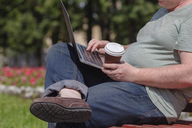 Empresário está sentado no parque e usando o laptop. homem de negócios usando o laptop ao ar livre