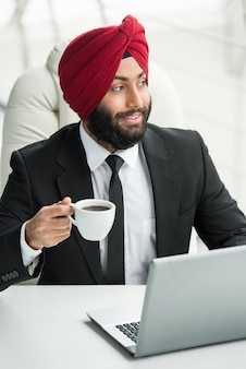 Empresário está trabalhando em seu computador no escritório.