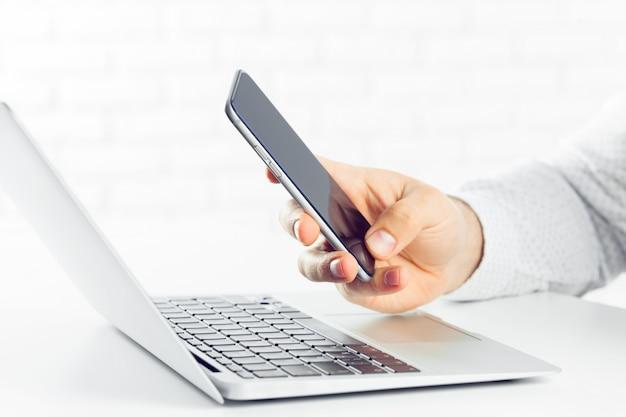 Empresário está usando o computador portátil e smartphone