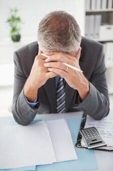 Empresário estressado com a cabeça nas mãos