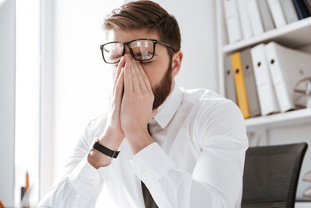 Empresário estressante no escritório tocando os olhos.