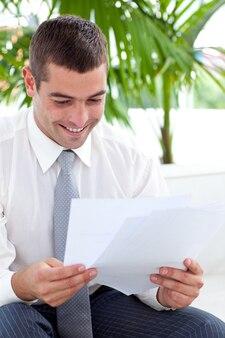 Empresário estudando alguns documentos no sofá