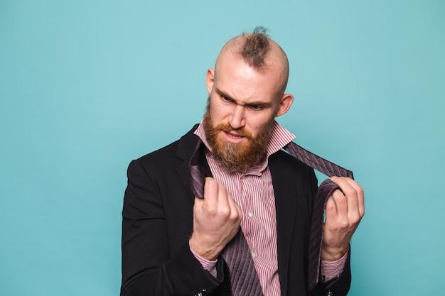 Empresário europeu barbudo de terno escuro isolado, zangado tentando amarrar uma gravata não sei como fazer