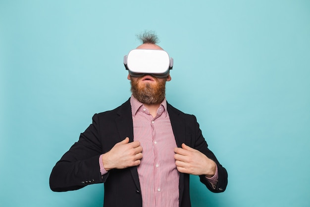 Empresário europeu barbudo em terno escuro isolado, animado e surpreso com o toque no ar usando óculos de realidade virtual