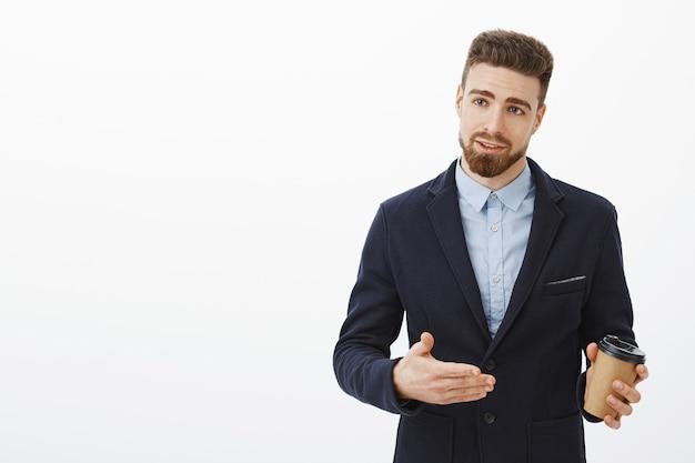 Empresário europeu bonito e confiante com barba e bigode em um terno elegante, gesticulando para discutir negócios, segurando o copo de papel de café, lidando com parceiros da empresa contra uma parede branca