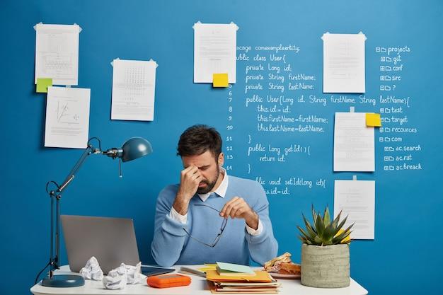 Empresário exausto esfrega o nariz, tira os óculos, sofre de cansaço visual e dor de cabeça, tem problemas no trabalho, senta-se no espaço de coworking com o computador laptop, parede azul com anotações escritas.