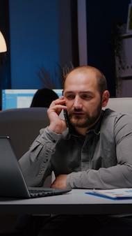 Empresário exausto, sentado à mesa da escrivaninha, discutindo ideias de gerenciamento
