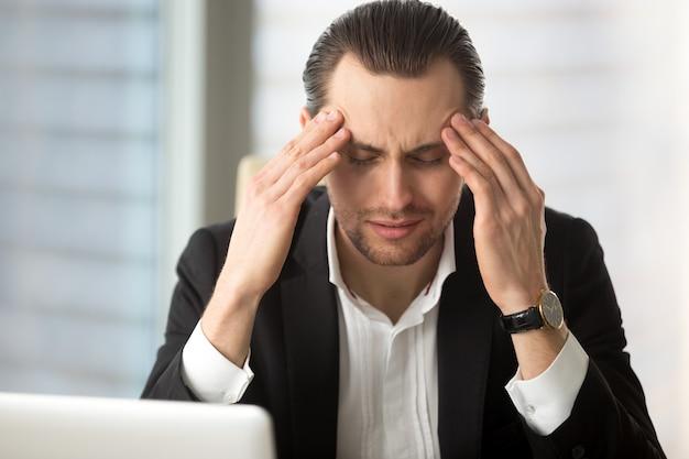 Empresário exausto, tendo uma dor de cabeça