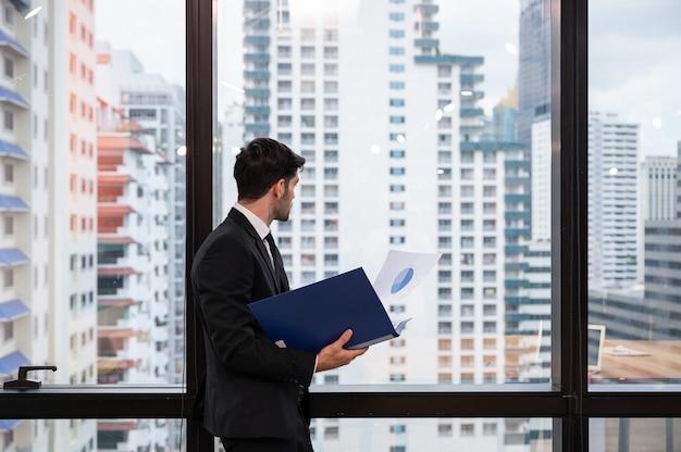 Empresário executivo inteligente caucasiano em pé segurando uma pasta de documentos e olhando o centro da cidade pela janela do escritório