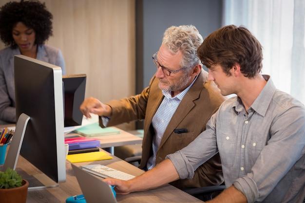 Empresário explicando colegas sobre o computador