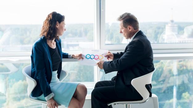 Empresário, explicando o gráfico ao seu colega do sexo feminino