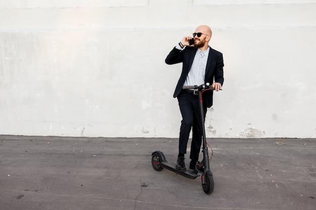 Empresário falando ao telefone, ao lado da scooter elétrica