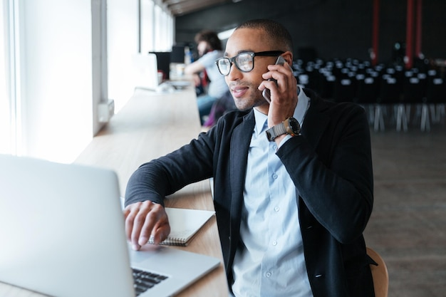 Empresário falando ao telefone e trabalhando usando um laptop no escritório