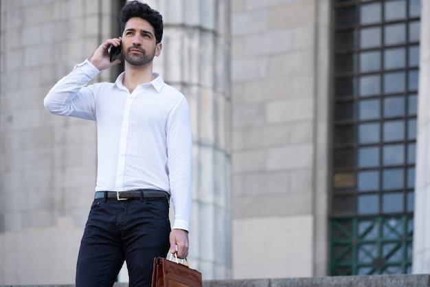 Empresário falando ao telefone em pé na escada ao ar livre. conceito de negócios.