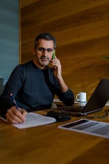 Empresário falando ao telefone enquanto escreve em um pedaço de papel em casa