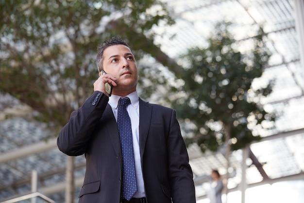 Empresário falando com celular em ambiente urbano
