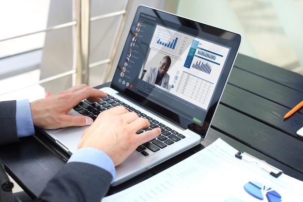 Empresário falando com seus colegas em videoconferência. equipe de negócios multiétnica trabalhando usando laptop, discutindo o relatório financeiro de sua empresa.