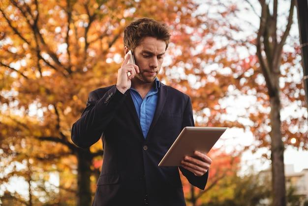 Empresário falando no celular e segurando o tablet digital