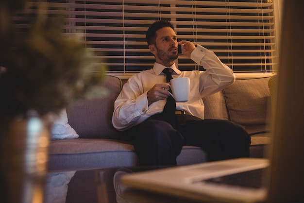 Empresário falando no celular enquanto toma café