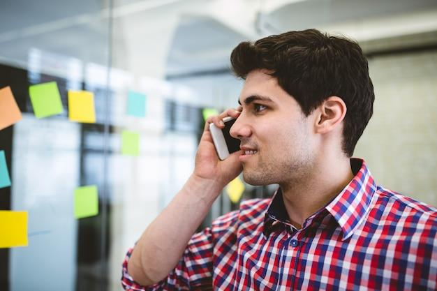 Empresário falando no telefone enquanto olha para as notas autoadesivas
