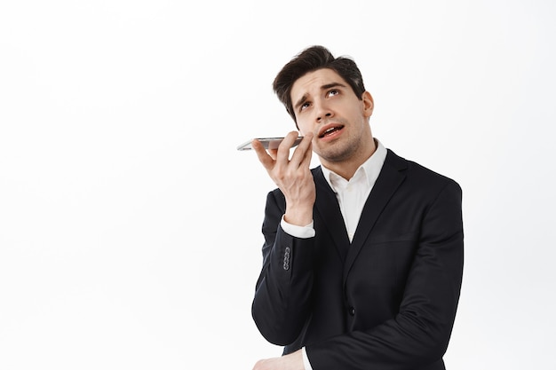 Empresário falando no viva-voz, olhar pensativo e gravar voz no smartphone, usando o aplicativo tradutor no celular, em pé sobre a parede branca
