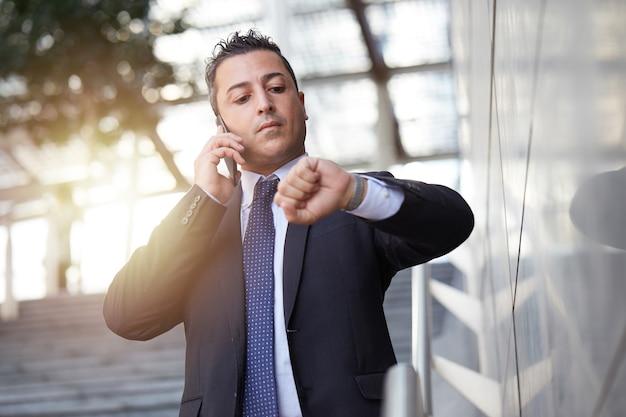Empresário falando para celular em ambiente urbano