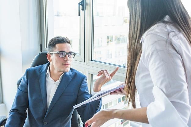Empresário, fazendo perguntas para mulher de negócios no escritório