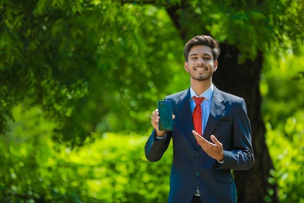 Empresário feliz apontando o dedo na tela em branco do smartphone